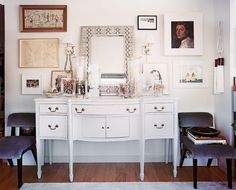 Gallery Wall - A gallery wall of art hung above a white sideboard and a pair of chairs