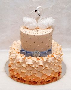 Beautiful peach frilled cake with swan toppers- I would do pale blue, gold and black though