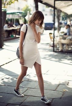 Street style. White cap sleeved, asymmetrical dress and sneakers