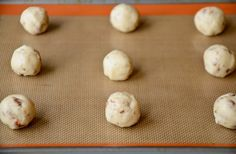 A baking sheet with balls of pecan cookie dough