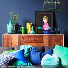 Die dunkelblaue Wandfarbe und die dazugehörigen Kissen in Türkis und Königsblau laden zum Einkuscheln ein. Farben wie Gelb und Grün, die auf der Farbskala neben Blau angesiedelt sind, passen gut ins Gesamtbild.