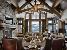 living room design with large fireplace and ceiling beams made of logs