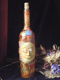 Hand Made Decoupaged Lighted Decorative Bottle with Polymer Clay Celestial Sun Plaque. $45.00, via Etsy.