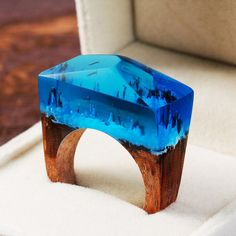 IF WINTER IS TO BEFALL, AT LEAST LOOK FORWARD TO A MIDNIGHT SNOWFALL.  This ring is made of light blue resin. The base is made from a white oak wood. The base is dark balau, a tropical timber found throughout Asia.