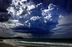 A giant storm cloud can be seen in the sky above swimmers near Mollymook Beach, south of Sydney March 5, 2014. REUTERS/David Gray