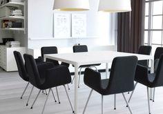 Sala de reuniones con sillas negras y mesa de vidrio negro/cromado