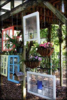 Gartendeko aus alten Fenstern mit bunt gestrichenen Rahmen