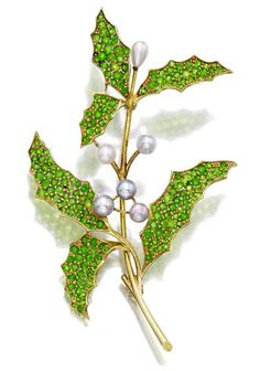 A demantoid garnet and natural pearl brooch designed as a polished gold branch, extending pavé-set demantoid garnet leaves, enhanced by cream and grey natural pearls; mounted in eighteen karat gold; length: (several demantoid garnet deficient) Garnet Jewelry, Gems Jewelry, Pearl Jewelry, Antique Jewelry, Vintage Jewelry, Fine Jewelry, Jewellery, Jewelry Box, Art Nouveau