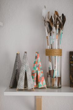 DIY chopstick tipis, and hand painted arrows from our woodland adventure themed nursery in grey, white, orange, and mint.
