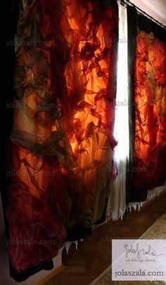 Zasłona wykonana z ciężkiego aksamitu. Połączenie z urzeźbioną leciutką tkaniną w intensywnych. ciepłych pomarańczach daje ciekawe zestawienie w każdym wnętrzu. Proszę zwrócić uwagę na specjalnie dobrane kolory, które powodują, że przechodzące przez nie światło nabiera jeszcze większego wymiaru.  on Jola Szala - Siła kobiecego ubrania  http://jolaszala.com/o-tkaninach1/okno/#sg18