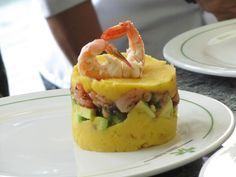 Causa Limeña: First Layer: Smashed yellow Potato(Papa Criolla) with sour cream and lemon juice. Second layer: avocato, Third layer: Shimps with katchup and coriander. Last layer as the first one. Big Shimp