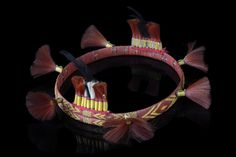 India, Naga, Sumi  bamboo ring, wrapped with orchid bast dyed in red, patterns in yellow, decorated with tufts of wild goats hair in red and black, black feathers