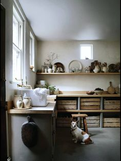 Beautiful rustic and vintage country kitchen. Old wooden crates, natural window light, mounted wall shelves. White, gray, slate, taupe, brown, wood.