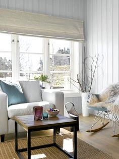 Lyse vegger og vinduskarmer er et fint utgangspunkt for å få detaljer i interiøret til å poppe frem. En hvit vase med knekte greiner, en turkis gyngestol i retrostil med lammeskinn og et bastteppe på gulvet.