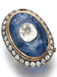 An antique sapphire and diamond ring, circa 1900. The oval sapphire inset with a cushion-shaped diamond, within a surround of circular-cut diamonds, central jewel detachable. #antique #ring