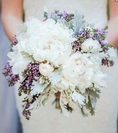 Loose clutch bouquet of cream hydrangeas, white peonies, ivory spray roses, grey dusty miller, and lavender sweet peas wrapped in ivory ribbon with the stems