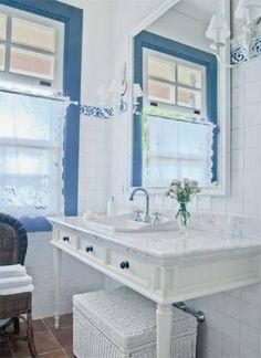 Romântica, a bancada do banheiro é uma mesa de madeira pintada com tampo de…