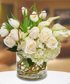 This elegant all-white design is a perfect fit for any occasion. Featuring white roses, miniature calla lilies, white tulips and hydrangeas in a round cylinder vase with curly willow tips, this magnificent bouquet will stand out with an added touch. Calla Lily Centerpieces, Wedding Centerpieces, Wedding Bouquets, Wedding Flowers, White Bouquets, Tall Centerpiece, Purple Wedding, Diy Wedding, Flower Arrangements Simple