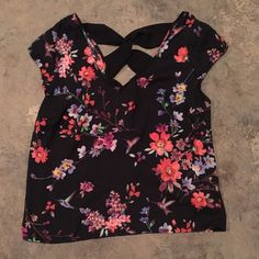 Express black floral top size XS NWOT Express black with floral pattern top. This top is NWOT and in excellent condition. It is a size XS and the body is made of 98% polyester and 2% spandex and the back trim is 100% polyester. This top is short sleeve and has a cute cris cross in the back. It would look great with some skinny jeans and wedges. Express Tops Blouses