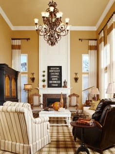 A white fireplace is the center of this formal great room with plaid carpeting, armchairs in leather and striped fabric, floor-to-ceiling curtains and an Old World-style chandelier.