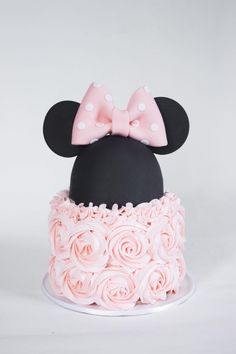 Beautiful Minnie Mouse cake with pink buttercream ruffles and a pink bow by Joni and Cake