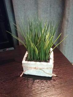 Vase carré en ciment où est piqué un à un dans une mousse florale des brins de verdure. De minuscules roches noires camouflent la mousse.