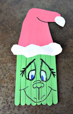 Create this super cute Popsicle Stick Grinch with your kids this holiday season. A perfect pairing with the classic book and movie. (via stick ornaments grinch Popsicle Stick Grinch Craft Popsicle Stick Christmas Crafts, Grinch Christmas Decorations, Grinch Christmas Party, Popsicle Crafts, Preschool Christmas, Christmas Crafts For Kids, Craft Stick Crafts, Christmas Projects, Holiday Fun