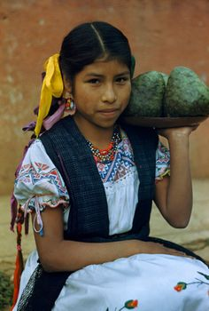 TINGAMBATO, MEXICO. A Purépecha girl in folk dancing costume holds tray of tree-grown cherimoyas. Photograph by Justin Locke.