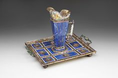 Renaissance Revival Lapis Lazuli Ewer & Tray, Hermann Böhm (Active 1866-1922) Maker(s): Hermann Böhm (Active 1866-1922) c. 1872-1922 Materials/Techniques: Silver-gilt, enamel and lapis lazuli Dimensions: Origin: Inventory #: 543 Inscription: Marked HB, A (Austria, tray), Guaranty Assay Mark for the Former Austro-Hungarian Empire (used 1872-1922, on tray) and purity dog's head mark for small articles (used 1872-1922, on ewer) Height of ewer 19.5 cm. • Tray 22 cm. X 30.5 cm.