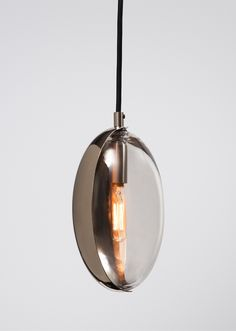 """Oona Mini is an artisan-crafted hanging pendant featuring a hand-finished, formed metal """"eyelid"""" which rotates around a blown glass form, revealing the polished finish of the lid's interior. The interior luster directs the lamp's glow. As it is set and reset, it transforms both itself and the space around it. Whether a single pendant or a grouping of multiples is commissioned, every installation is unique and made to order."""