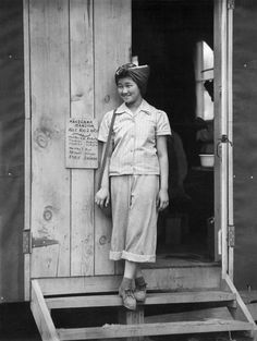 A young woman in the doorway of her barrack apartment at this War Relocation Authority center for evacuees of Japanese ancestry. Manzanar, California, 1942.
