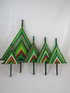 For your consideration: Vintage Gods Eye Christmas Tree Set    Here is a set of five Gods Eyes fashioned into Christmas trees. Each tree features two square green dowels that serve as the skeleton for the yarn to be wrapped around. Several shades of green, solid red, white, and a variegated red and white yarn are all carefully and neatly wrapped around the dowels to form a modern tree. The dowels are meant to be inserted into a plant or other medium that will provide stability, as they wont…