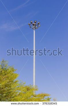 Sport lights post in public garden with green tree and blue sky background - stock photo