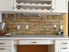 Two deconstructed pallets find new life as a horizontally installed desk backsplash in a kitchen. The boards are painted with a whitewash and highlighted with the bright wall color.  Design and installation by HDD.