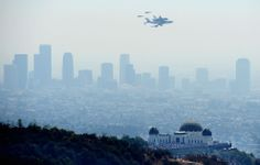 The Space Shuttle Endeavour, mounted atop NASA's modified Boeing 747, flies above Griffith Park Observatory in Los Angeles on its final flight, on September 21, 2012.  (photo: Joe Klamar/AFP/Getty Images)