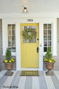Bright door with fantastic wreath, flanked by matching flowers in urn style planters