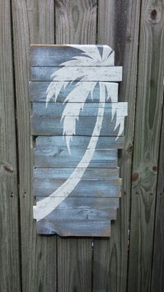 A simple silhouette  of a palm tree painted onto a rustic wood board.