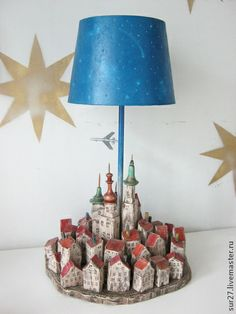 Лампа `Город`. В основании светильника - город. Абажур - звездное небо с дырочками, которые при включенной лампе становятся звездами. Под абажуром на незаметной леске парит самолетик.