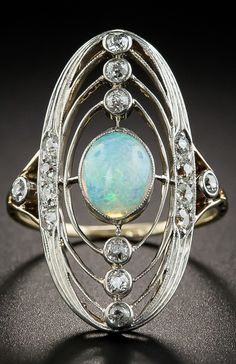 An antique platinum-topped gold, opal and diamond ring. Reminiscent of an armillary sphere, this celestial jewel, dating back to the first or second decade of the twentieth century, centres on an earth-like opal elliptically orbited by twinkling diamonds.