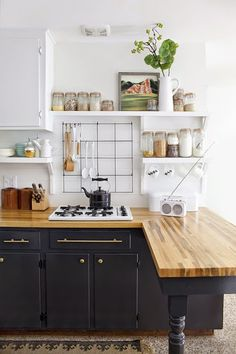 LOVE this kitchen, the counter top stove, black accents, radio, everything!