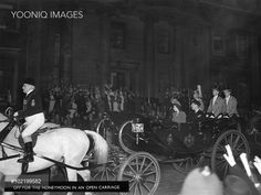 Princess Elizabeth (Queen Elizabeth II) and her new husband, Prince Philip, Duke of Edinburgh leave Buckingham Palace in an open carriage to embark on their honeymoon which would be spent at Broadlands in Hampshire.