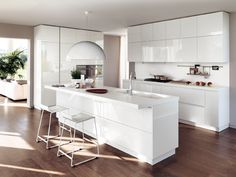 "LiberaMente by #Scavolini.The Prestige  White glossy lacquered #kitchen outlines a separate ""centre of the house"" that still  interacts and communicates with the  other areas; a composition enhanced by an essential design, concealed functionalities, a pure colour and lots of light flowing in. #livingroom"