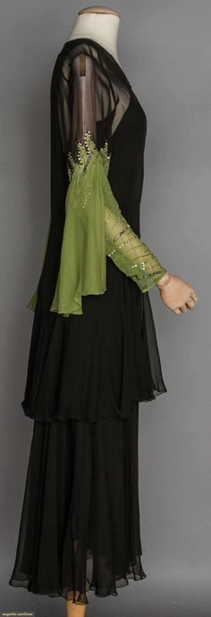 EVENING GOWN, 1930s. Black silk chiffon, drop W w/ flounce, long sleeves top 1/2 black, bottom 1/2 beaded pea green w/ attached flounce. Sideway