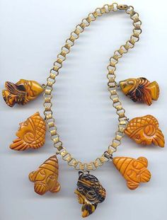 Brass & carved marbled Bakelite warrior style faces necklace.