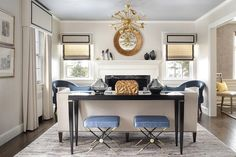Two blue Jonathan Adler Rider Benches sit on a gray rug under a black sofa table topped with a Arteriors Baroque Antiqued Gold Leaf Lidded Box located behind an ivory sofa illuminated by a Jonathan Adler Sputnik Pendant. Robert Abbey cornice boxes roman shades