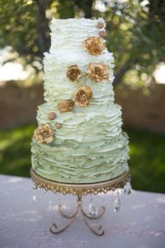 White to green ombre ruffled wedding cake with gold flowers