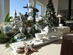 Great vignette for coastal Christmas ... love the reindeer, silver pots, white flora and greenery.