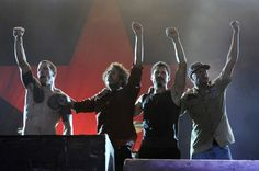 This image shows the band raising their fists which communicates solidarity, resistance, strength and is a symbol of unity.