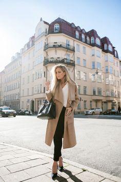 Shop this look on Lookastic:  https://lookastic.com/women/looks/coat-long-sleeve-blouse-skinny-pants-pumps-tote-bag/5081  — Black Suede Pumps  — Black Skinny Pants  — Black Leather Tote Bag  — White Long Sleeve Blouse  — Camel Coat