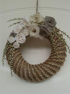 Ghirlanda di cannucce di carta lavorata a spirale con decoro di fiori di vari tessuti.